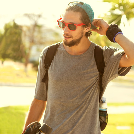 Hipster style guy. Fashion man on street palm at sunset