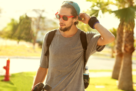mode: Hipster Stil Kerl. Mode Mann auf der Straße Palme bei Sonnenuntergang