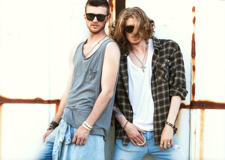xwhite: fashion guys friends sitting on the grass, wood backgrounds, sunset Stock Photo