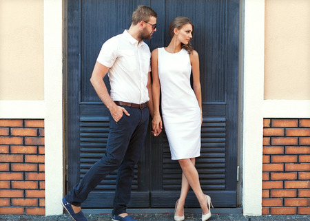 fashion couple standing in the European quarter, in a white dress, posing love at sunset.