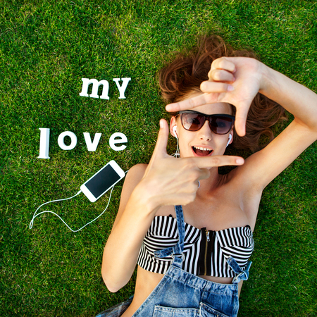 trave: girl lying on the green grass, makes a stop frame arms, listening to music on a white label trave- My Love Stock Photo