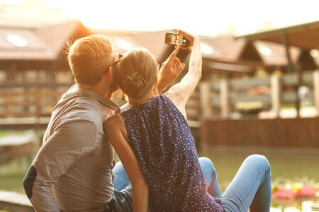 cell phones: couple in love sitting in the park at sunset makes the selfie Stock Photo