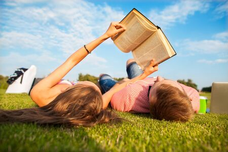 people relax: girl and guy lying on the grass reading a book relaxing in the park Stock Photo
