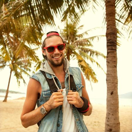 ipster style guy. Fashion man on street palm at sunset Foto de archivo