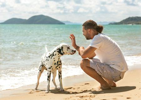 love park: man with dog on the tropical beach Stock Photo