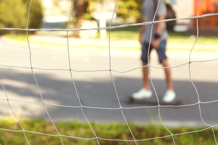 soccer net: man riding a skateboard in the street, the view through the soccer net