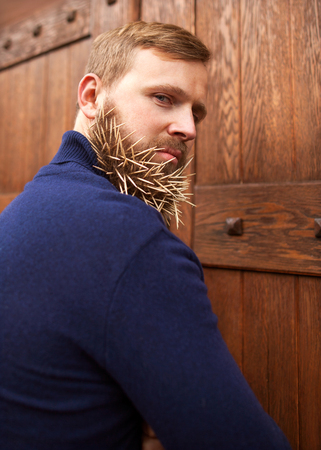 hatred: fashion hipster guy standing near a wooden door toothpicks in his beard, hatred, anger, contempt, deceit, greed.