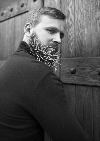 contempt: chico inconformista manera que se coloca cerca de una puerta de madera mondadientes en la barba, el odio, la ira, el desprecio, el engaño, la avaricia.