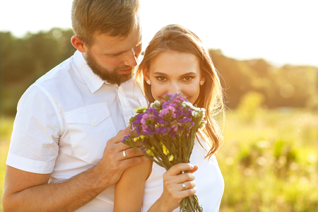 couple in love on nature, the guy kisses the girl on the cheek, and gives her flowers Foto de archivo