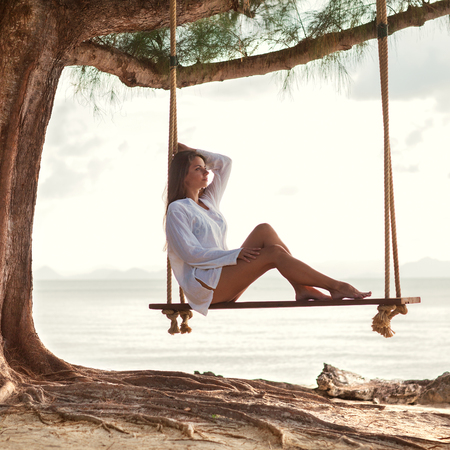 Girl on the swing on Koh Samui under the palm trees Stock Photo