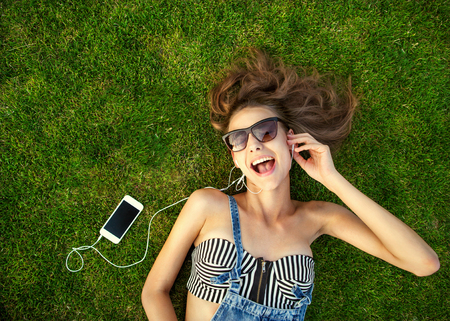 girl lying on the green grass, listening to music Stock Photo
