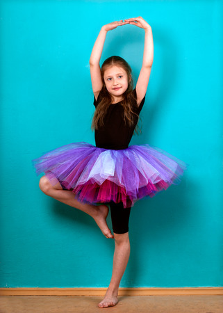 Little girl dreams of becoming ballerina in a tutu skirt violet