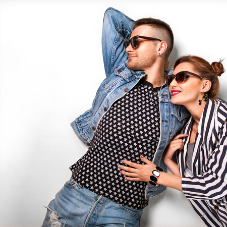 xwhite: Fashion couple in sunglasses lies on a white background, smiling happily and surprised. Vogue Style