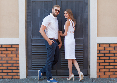 xwhite: fashion couple standing in the European quarter, in a white dress, posing love at sunset.