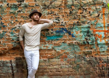 xwhite: Hipster style guy. Fashion man standing near wall