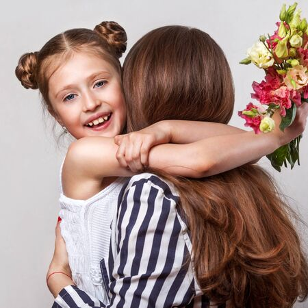 xwhite: Daughter gives her mother flowers in the studio, happy mothers day Stock Photo