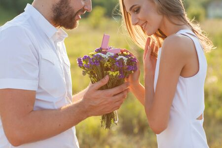 Guy gives a girl flowers, in love, romance, engagement concept