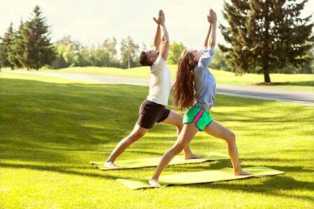 Pareja haciendo yoga en un hermoso campo verde de parque Foto de archivo