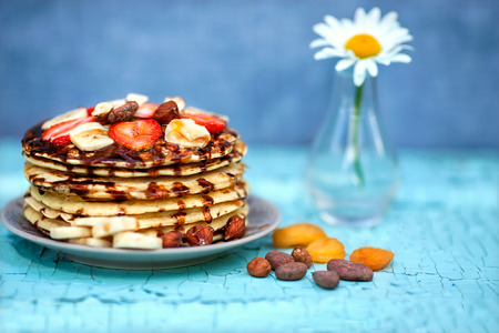 Pancakes with strawberries and banana drizzled with chocolate, standing next to bowl of camomile