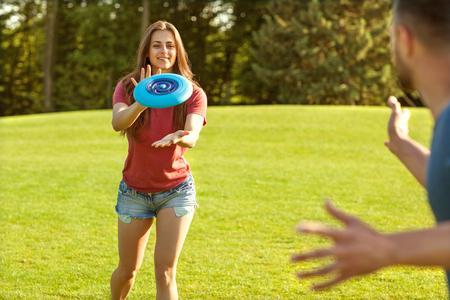 casal apaixonado jogando frisbee no parque, o conceito de um estilo de vida saudável.