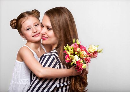 daughter gives her mother flowers in the studio, happy mothers day? daughter gives her mother flowers in the studio, happy mothers day? daughter gives her mother flowers in the studio, happy mothers day Stock Photo