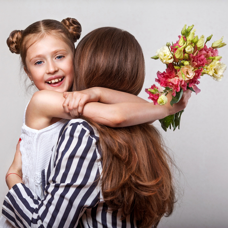 Daughter gives her mother flowers in the studio, happy mothers day Stock Photo