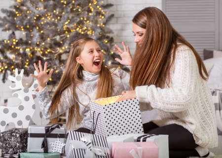 Young mother and her ittle daughters opening a magical Christmas gift by a Christmas tree in a cozy living room in winter