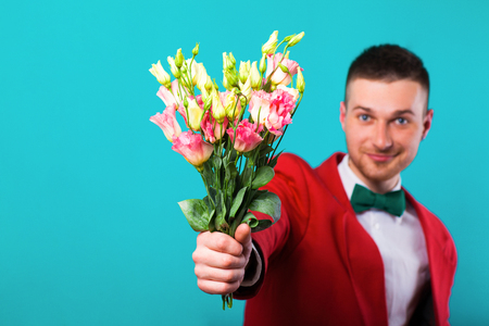 man holding flowers on Valentines Day, turquoise background