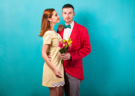 hipster couple in love with a bouquet of flowers in the studio at Christmas, the concept of Valentine's Day Foto de archivo