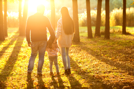 family with little daughter spend time in autumn park at sunset, back view Standard-Bild - 95411927