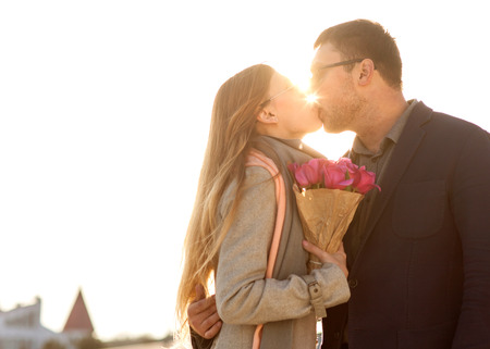 couple in love are facing each other on the day of the holy valentine, the guy gives a bouquet.