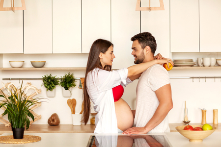 pregnant couple standing in their kitchen preparing
