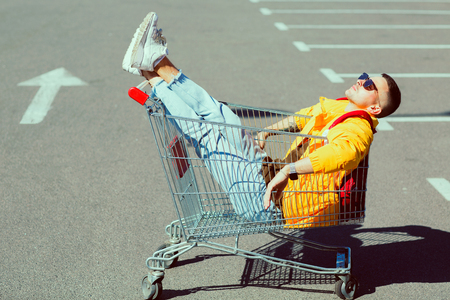 fashion guy in sunglasses and a yellow jacket sits in a cart from food in the supermarket parking