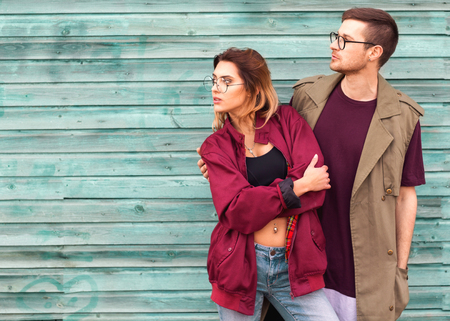 fashion couple in their glasses with burgundy clothes posing on a blue wooden wall Stock Photo