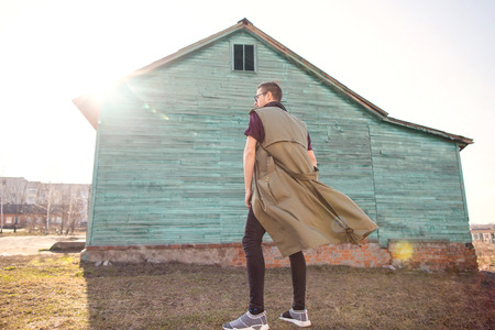 fashionable guy with glasses standing near a wooden house