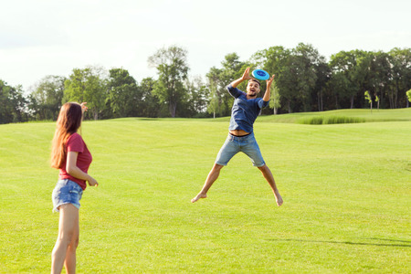 couple in love playing flying disk in the park, the concept of a healthy lifestyle. 版權商用圖片