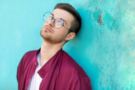 fashion hipster guy in glasses poses near the wall the color of the wave at sunset Banco de Imagens