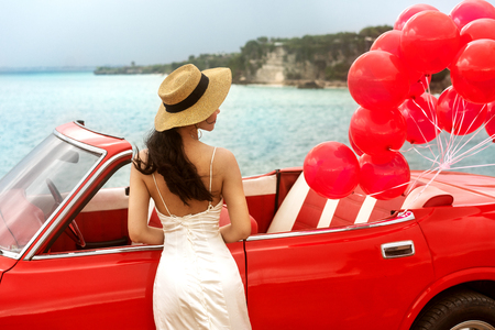 girl at the wedding in a white dress stands near the red retro car