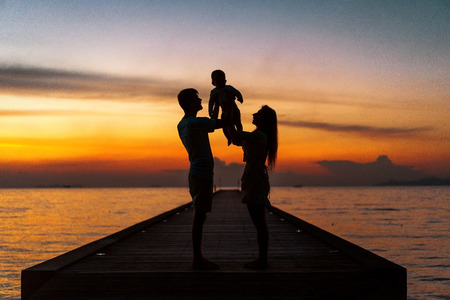 Family in love with son hugging at sunset, silhouette.
