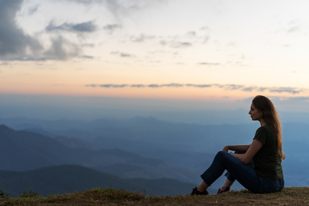 girl sitting in the mountains on the sunset