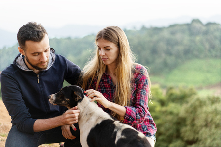 couple in love with a dog in the mountains Stock Photo