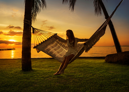 girl in a hammock bother palm trees enjoying a tropical vacation
