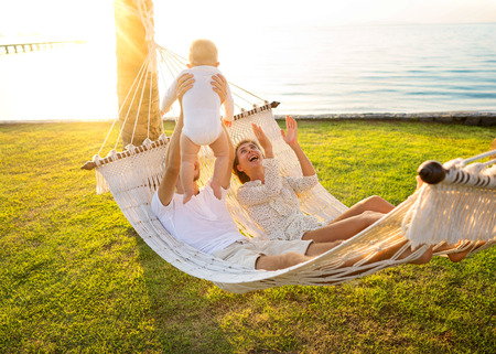 happy family on a tropical island at sunset lie in a hammock and play with their son Stock Photo