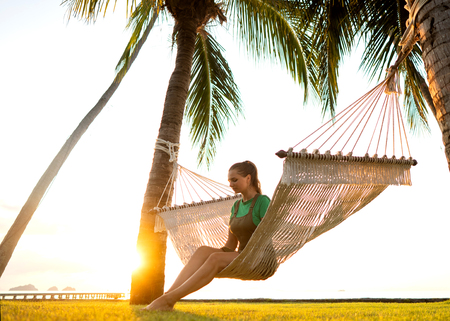girl in a hammock tropical palm trees enjoying a  vacation at sunset Stock Photo