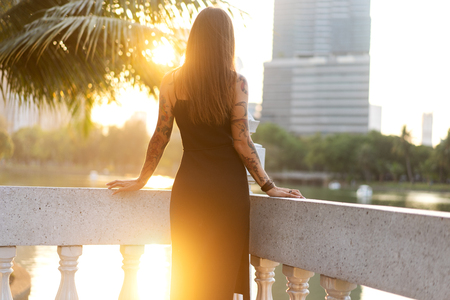 fashion girl standing at sunset in tropical palm trees Stock Photo