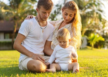 gelukkige familie op tropisch eiland bij zonsondergang spelen met zoon Stockfoto