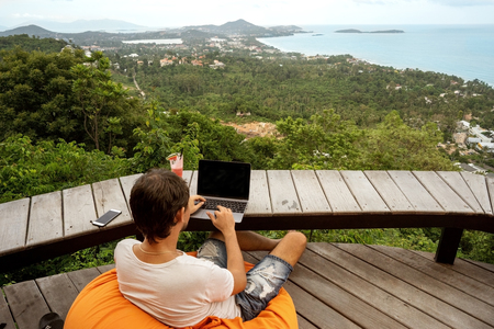 freelancer guy sits working with a view of Samui island and the mountains
