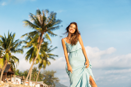 girl walks on a tropical beach in a dress