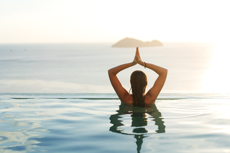 girl in the pool at sunset doing yoga with a view of the mountains and the sea Stock Photo