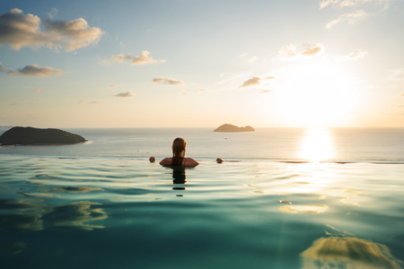 girl in the pool at sunset with views of the mountains and the sea